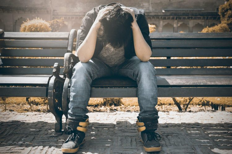distressed teen male on park bench
